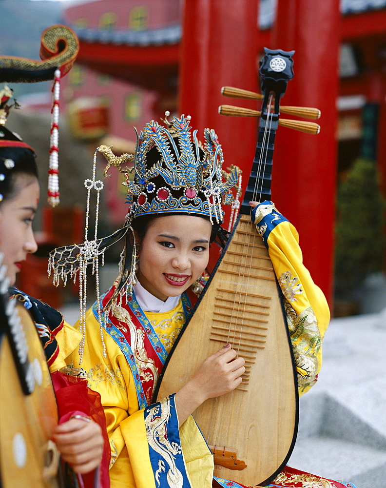 Woman dressed in traditional costume playing a three stringed lute, Beijing, China, Asia