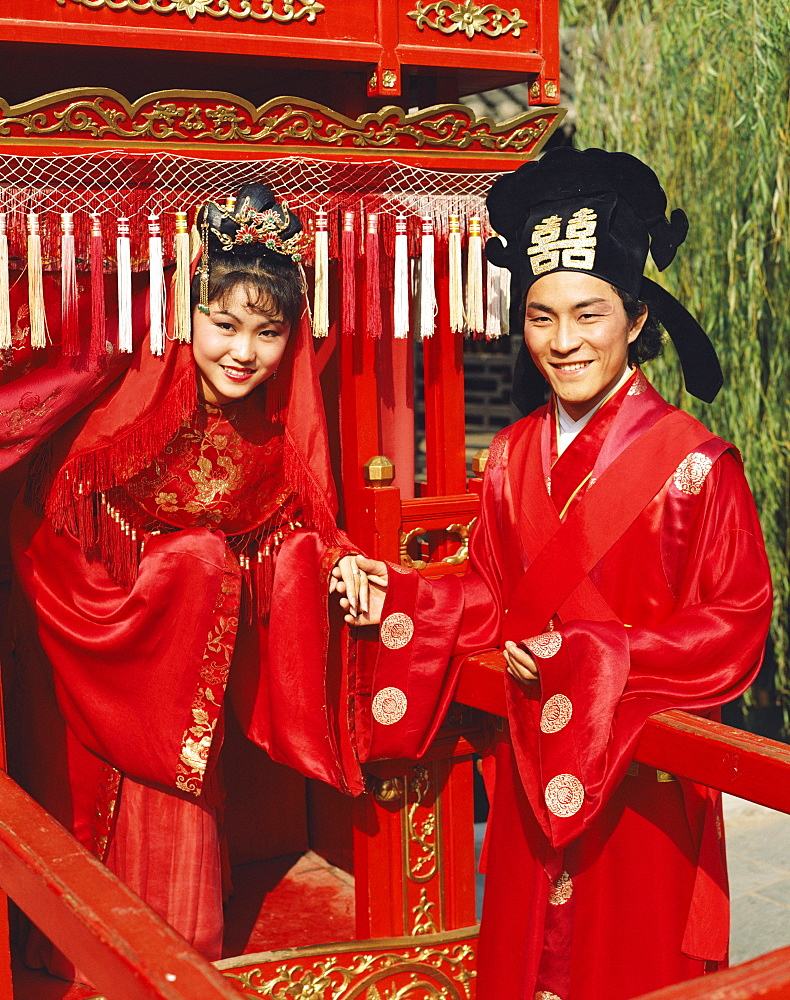 Man and women dressed in traditional wedding costume, Beijing, China, Asia
