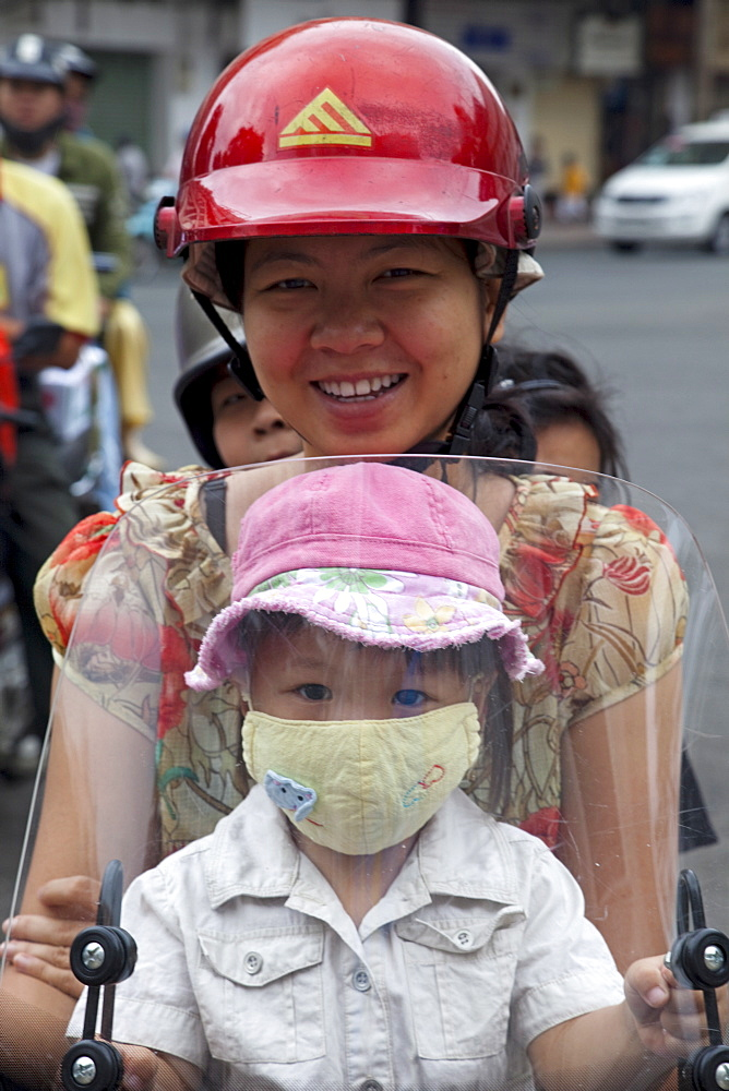 Motorbike passengers wearing pollution mask, Ho Chi Minh City, Vietnam, Indochina, Southeast Asia, Asia