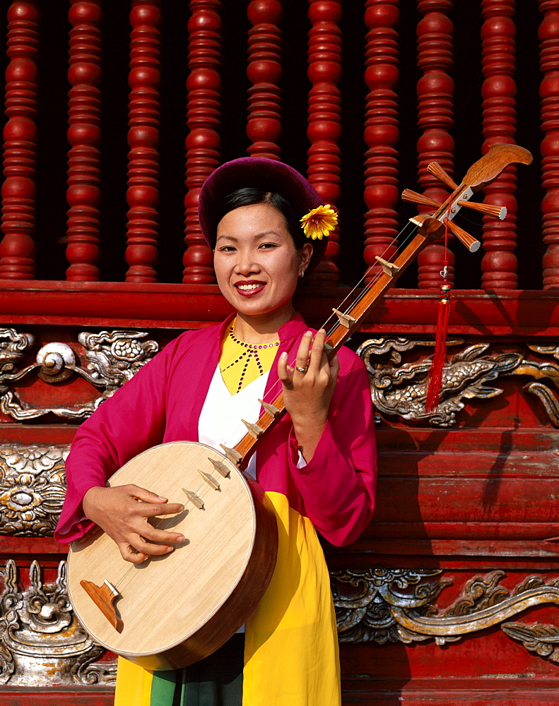 Woman dressed in traditional costume playing a stringed lute, Temple of Literature, Hanoi, Vietnam, Indochina, Southeast Asia, Asia