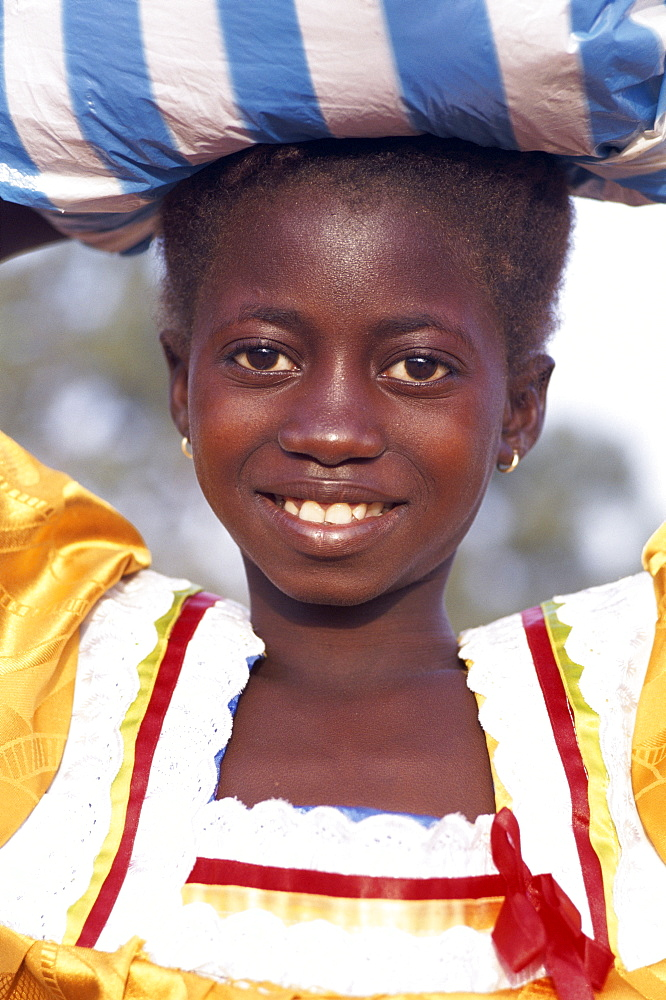 African girl carrying sack on head, Banjul, Gambia, West Africa, Africa