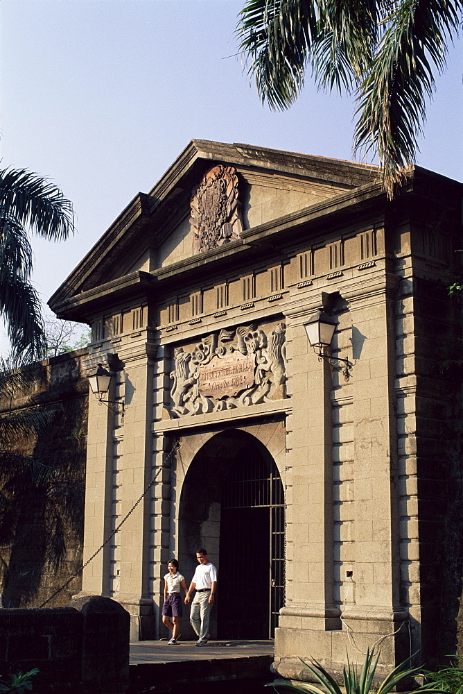 Couple walking through Puerta del Parian, one of the entrances to the Intramuros Historical District, Manila, Philippines, Southeast Asia, Asia
