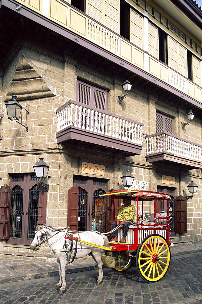 Calesa (horse drawn carriage) and Spanish colonial building in the Intramuros Historical District, Manila, Philippines, Southeast Asia, Asia