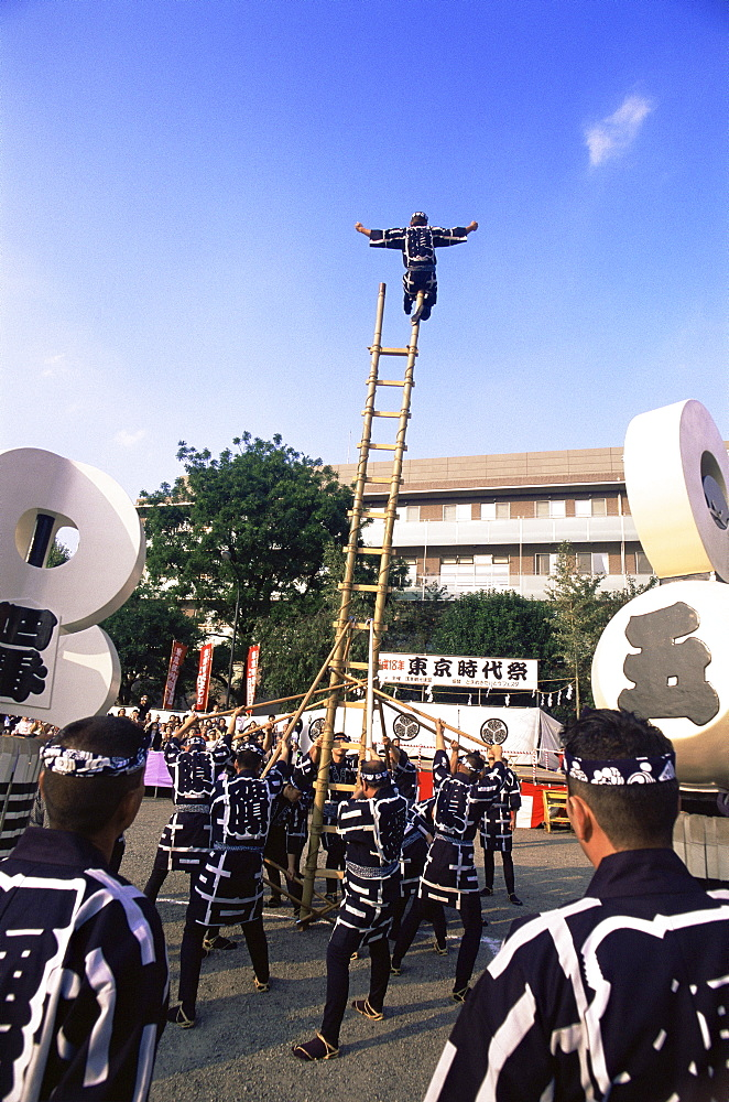 Acrobatic display by firemen at Jidai Matsuri Festival held annually in November at Sensoji Temple, Asakusa, Tokyo, Japan, Asia