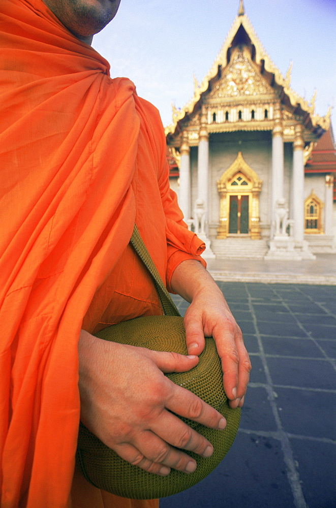 Monk holding alms bowl with temple in the background, Wat Benchamabophit (Marble Temple), Bangkok, Thailand, Southeast Asia, Asia - 834-5405