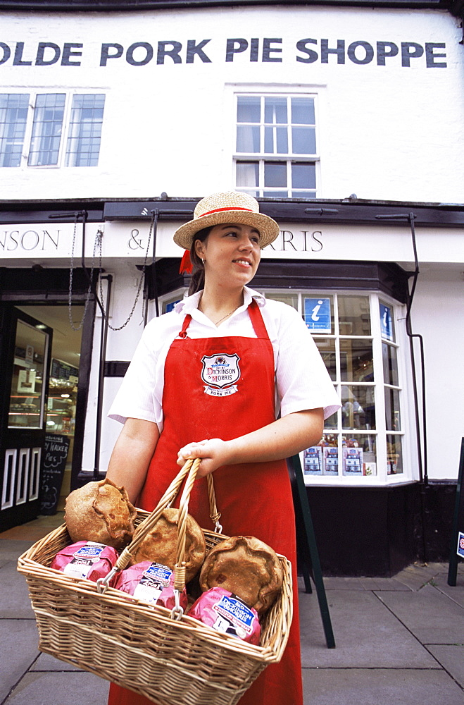 Sales girl holding basket of Melton Mowbray pork pies in front of the Olde Pork Pie Shop, Melton Mowbray, Leicestershire, England, United Kingdom, Europe