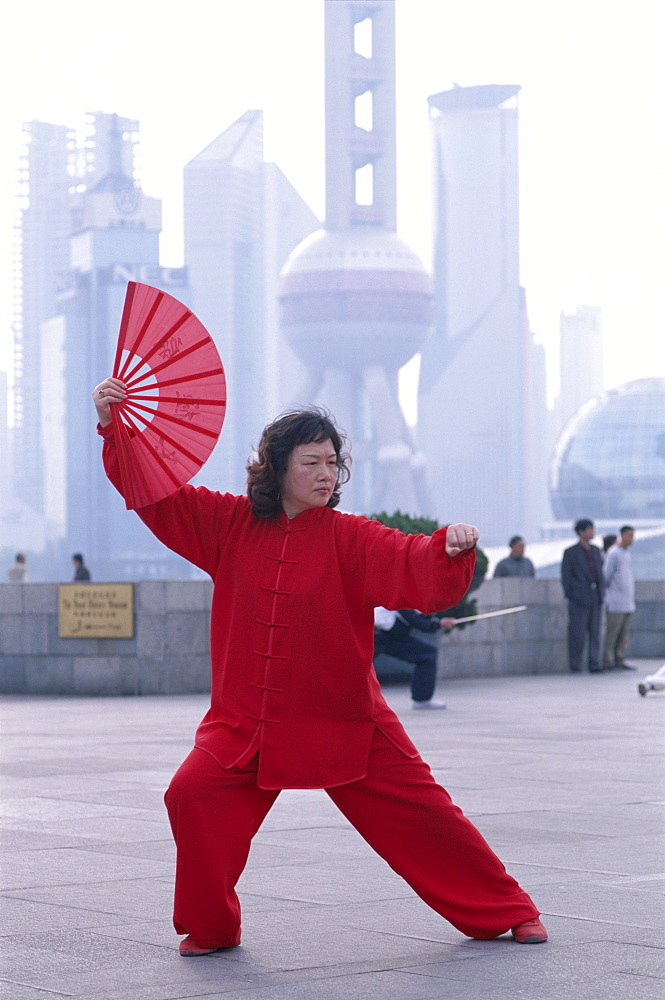 Woman doing martial arts on the Bund, with Pudong skyline in background, Shanghai, China, Asia
