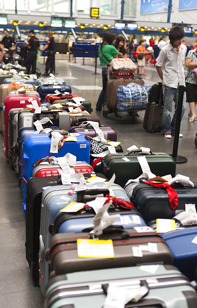 Airline passengers and luggage line up on the floor at the Beijing Capital Airport, Beijing, China, Asia - 839-23