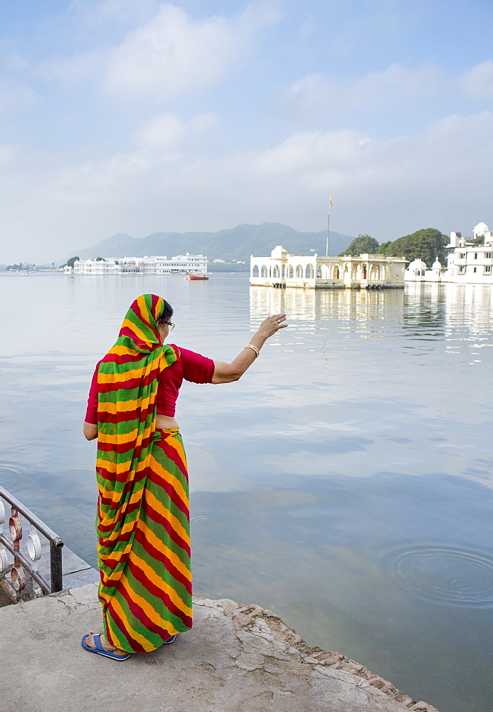 In the soft morning light, a Rajasthani woman in a sari looks over Lake Pichola, with the famous Lake Palace in the background, Udaipur, Rajasthan, India, Asia