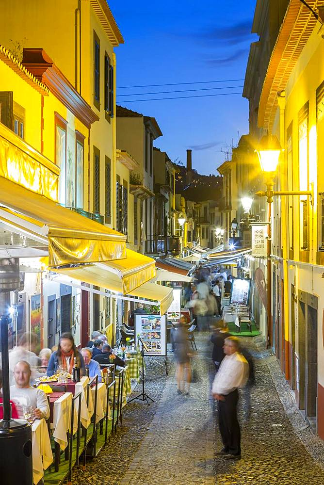 View of cafes in cobbled street in old town at dusk, Funchal, Madeira, Portugal, Europe
