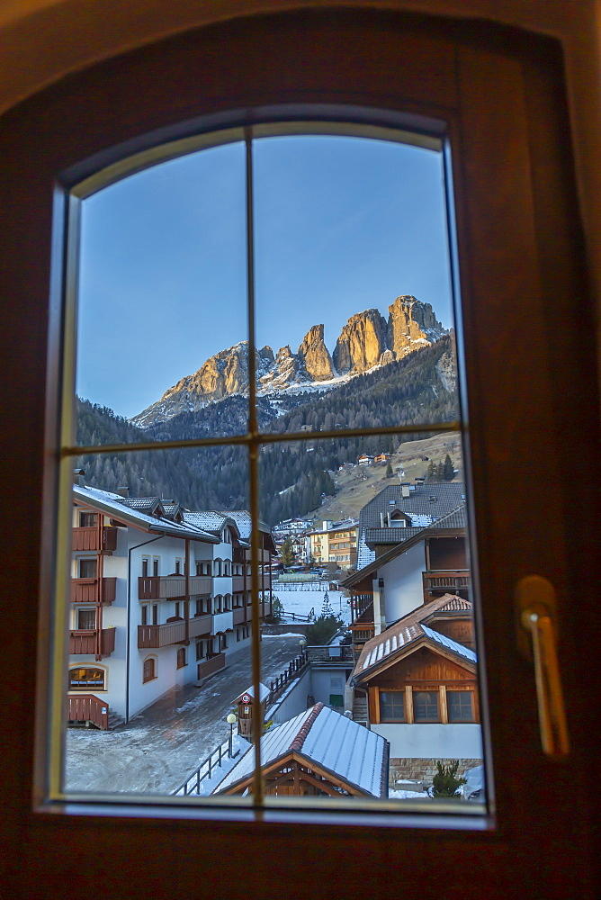 Window view of snow covered Campitello di Fassa and Grohmannspitze Punta Grohmann, Val di Fassa, Trentino, Italy, Europe