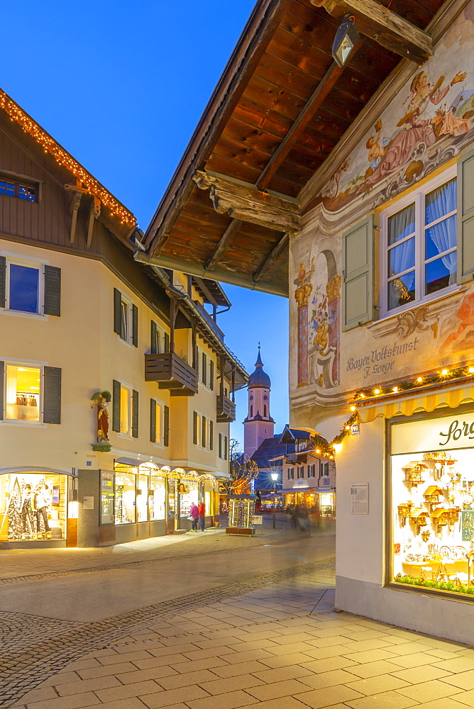 View of Parish Church of St. Martin and town shops at dusk, Garmisch-Partenkirchen, Bavaria, Germany, Europe