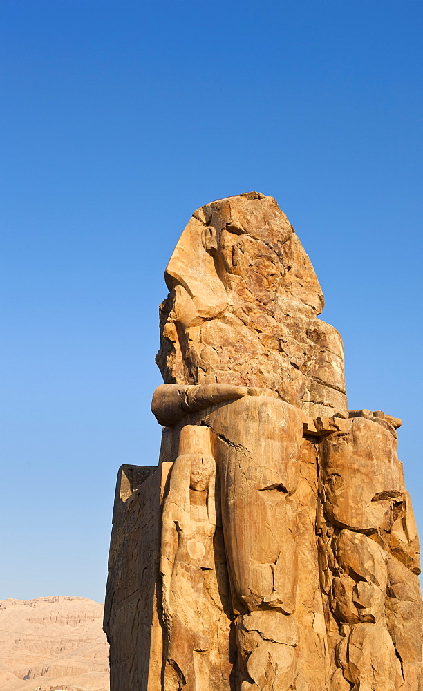 One of the Colossi of Memnon with the Theban hills behind, Thebes, UNESCO World Heritage Site, Egypt, North Africa, Africa