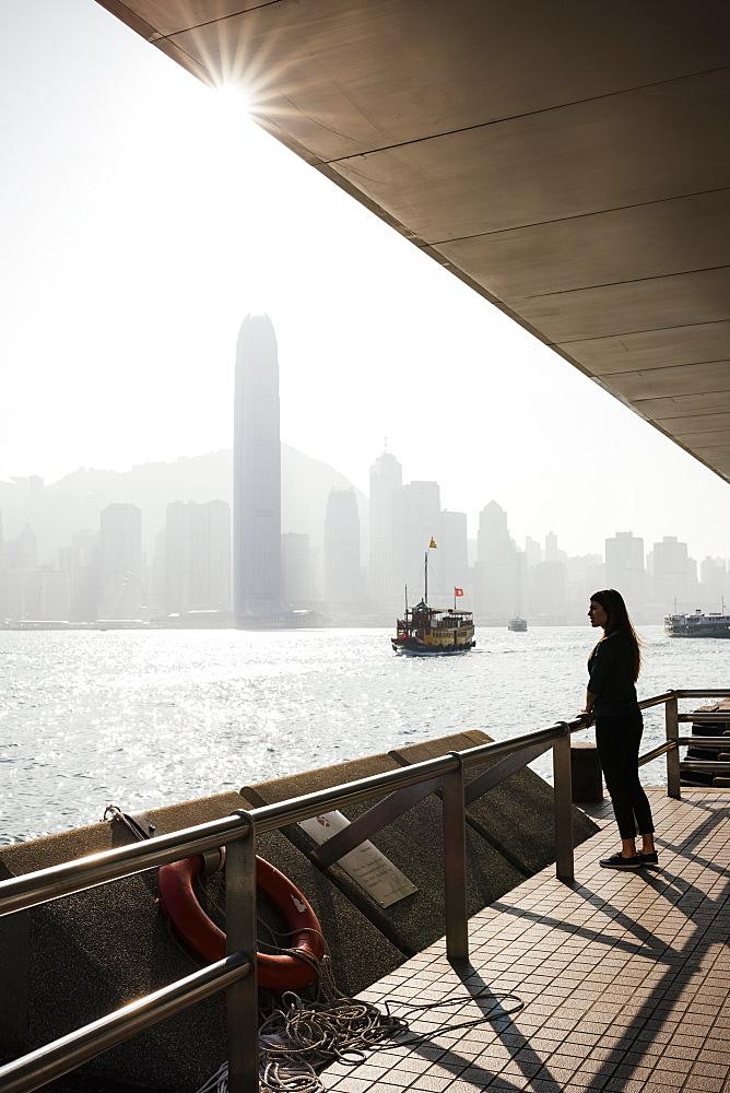 Young woman standing on Tsim Sha Tsui Waterfront, Kowloon, Hong Kong, China, Asia