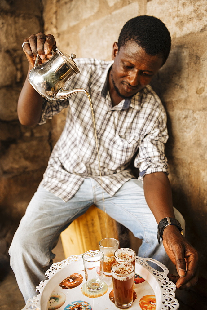 Man pouring traditional tea in Accra, Ghana, Africa