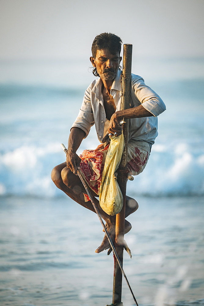 Stilt Fisherman at dawn, Weligama, South Coast, Sri Lanka, Asia