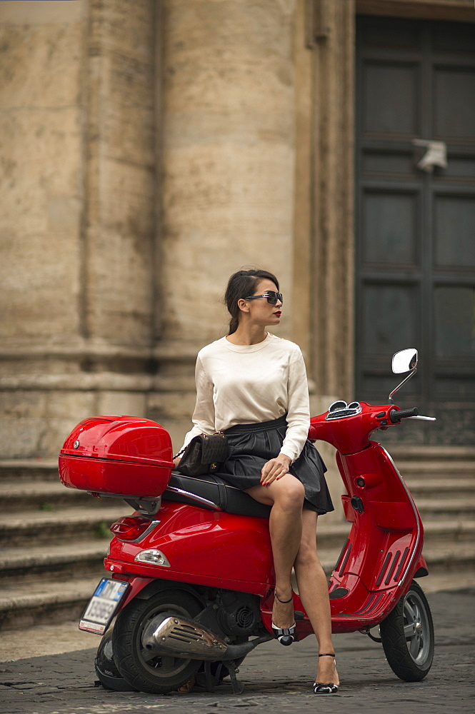 Young woman waiting by Vespa moped, Piazza del Popolo, Rome, Lazio, Italy, Europe