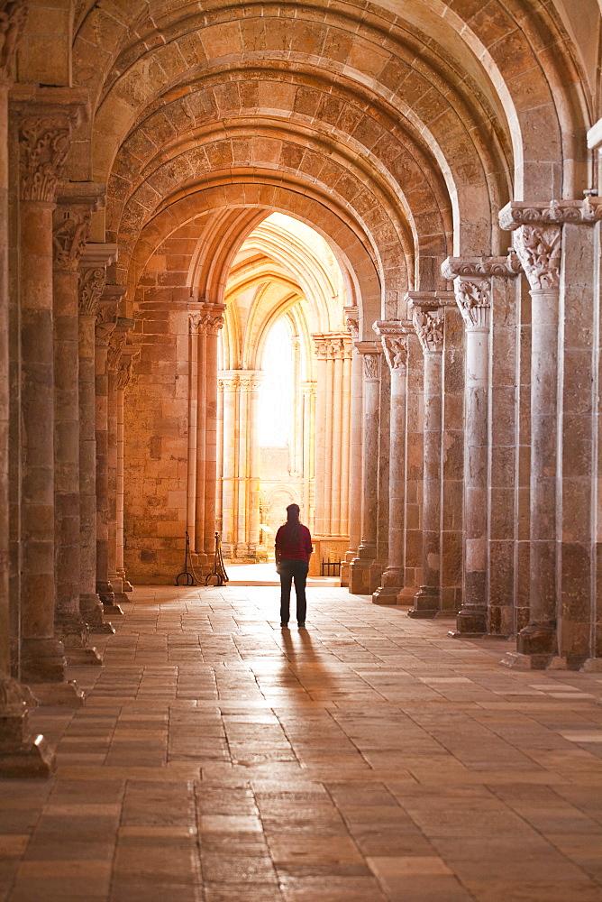 A lady slowly walks down an aisle in the Basilique Sainte-Marie-Madeleine of Vezelay, Yonne, Burgundy, France, Europe