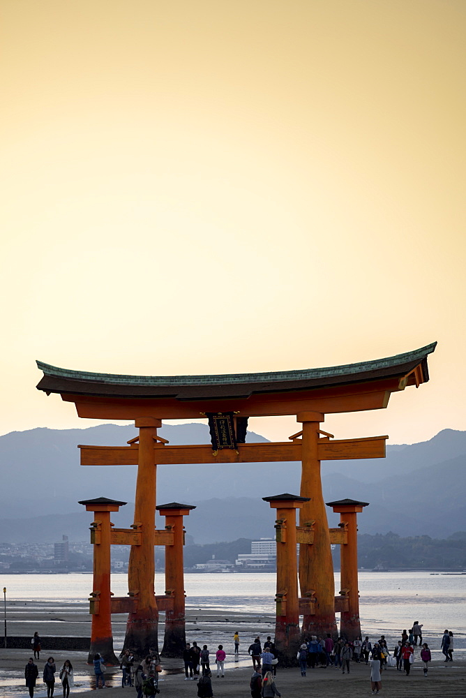 Tourists walking under the torii gate of Miyajima at low tide, Itsukushima, UNESCO World Heritage Site, Hiroshima Prefecture, Honshu, Japan, Asia