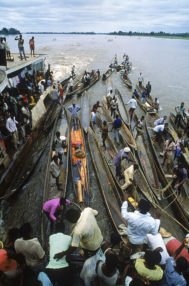 Some of the hundreds of dugout canoes or pirogues that are paddled out to tie onto the boat and barges that steam up the congo River. People who live along the river bring bush meat, fish, and produce to trade with the merchants who travel on the boat.