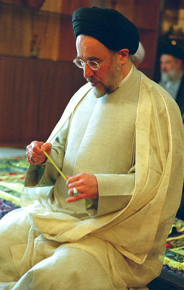 President Mohammad Khatami grasps his worry beads at Sa'd Abad Palace as he and fellow reformist pray after a landslide victory in the 2001 presidential elections.