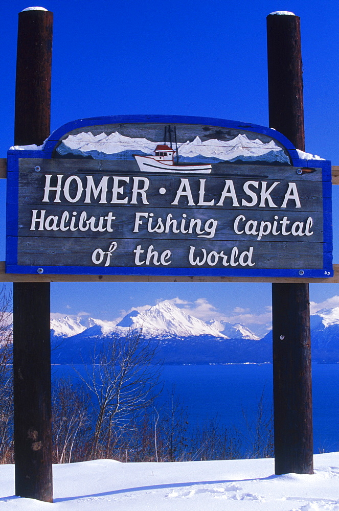 A wooden sign and a view of Kachemak Bay greets visitors at Homer, Alaska. The small Kenai Peninsula town boasts that it is the