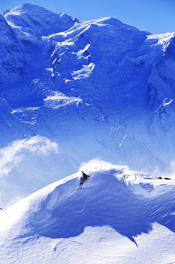 Early one winter morning, a snowboarder makes a turn underneath Mt. Blanc, Europest tallest mountain. Chamonix, France.