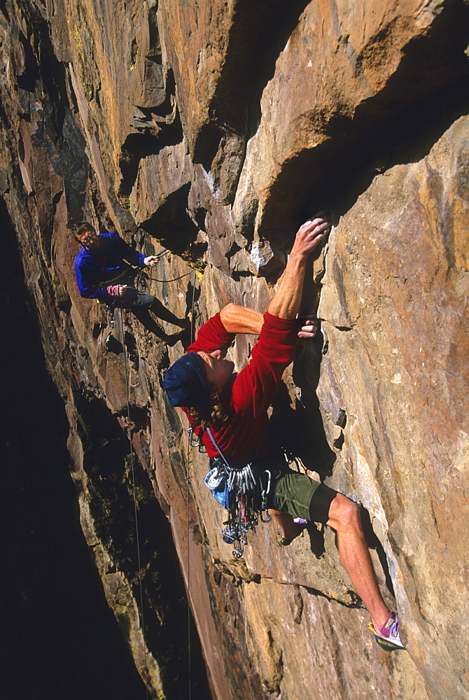 """Bruce Miller rock climbing on the route """"The Wisdom"""", rated 5.11b, while his partner Steve Dieckhoff belays, on the Redgarde"""