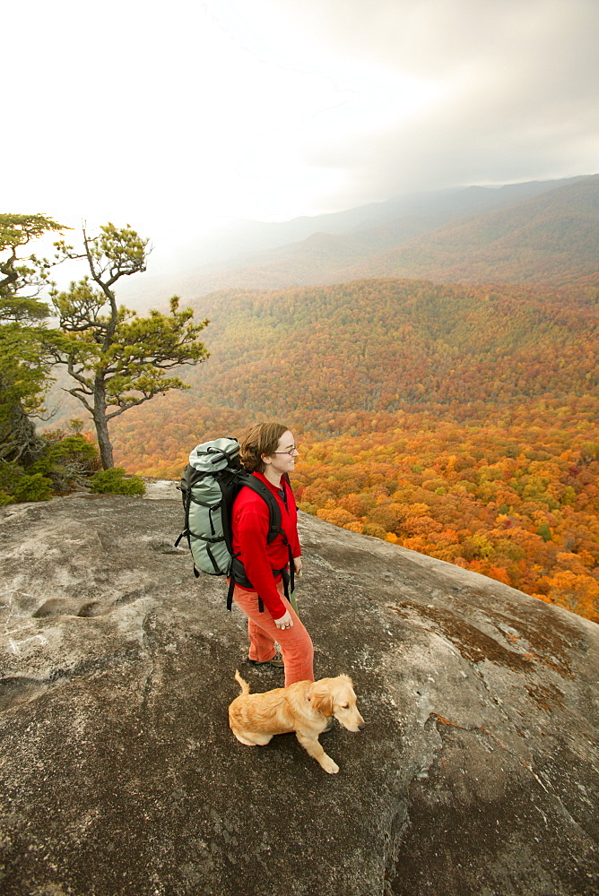 Katie Cavert and Oliver (golden retriever) check out the fall colors from atop Looking Glass Rock in the Pisgah National Forest near Brevard, NC.