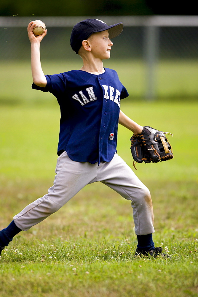 Harrison Walsh throws the ball to the third baseman during an a youth baseball game in Bolton, Ct.