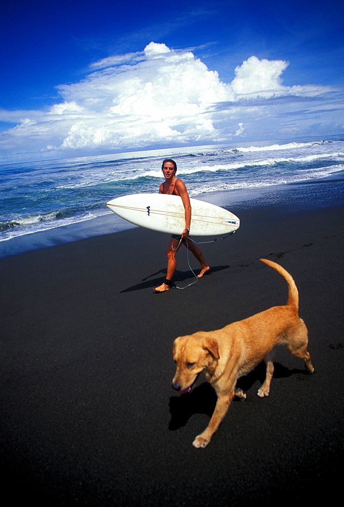 Pope Baskerville and her dog enjoy a leisurely day of surfing at Playa Hermosa, Costa Rica. Playa Hermosa is known for its powerful beachbreak and has one of the most consistent wave breaks in Costa Rica.