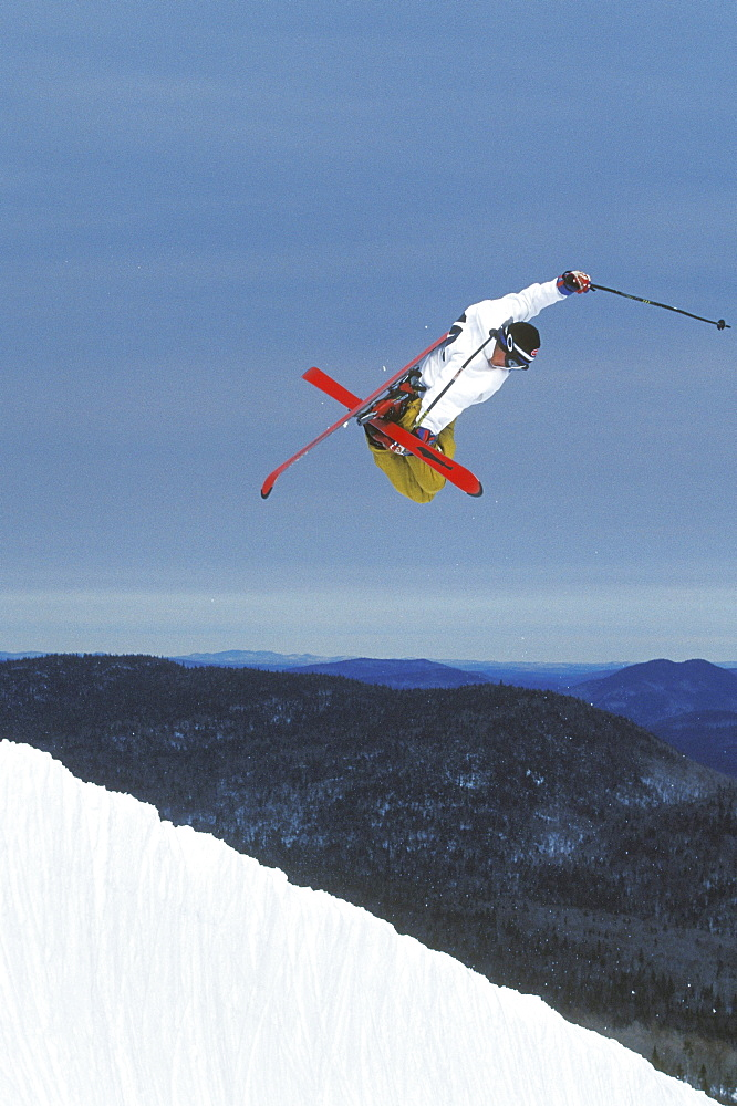 """Young male skier (Garrett Brittain) performs a """"mute grab"""" in the halfpipe at Mont Tremblant, Quebec, Canada."""