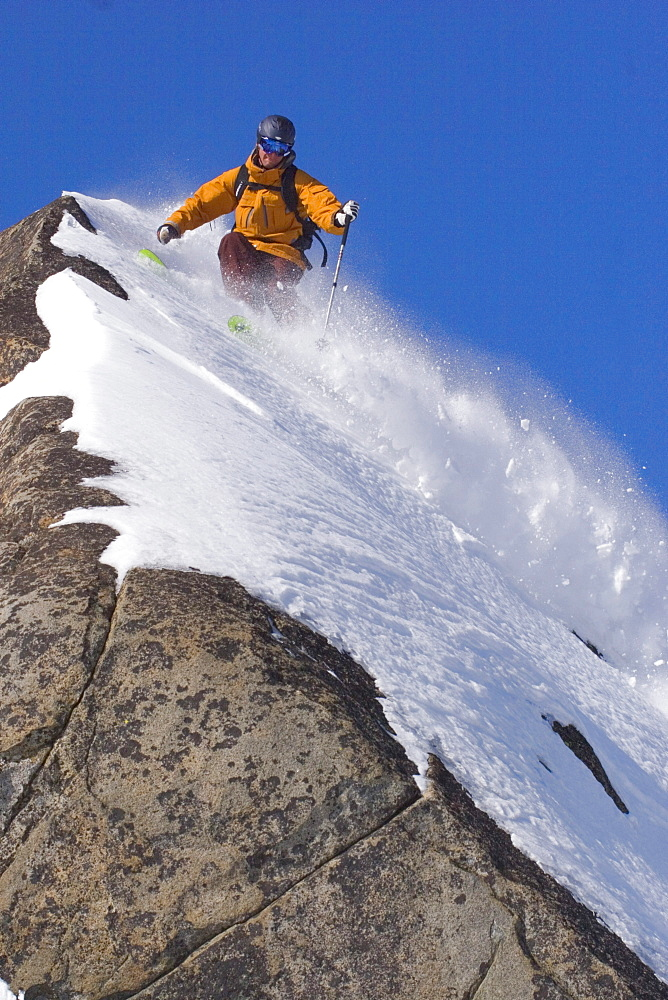 A man skiing powder snow on a rock on Donner Summit in California.
