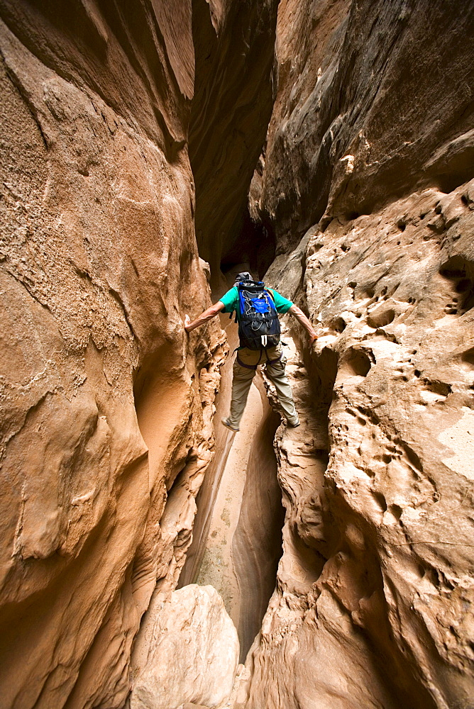 Jeff Crystol scrambling down the North Fork of Robbers Roost Canyon, Robbers Roost Country, Utah.