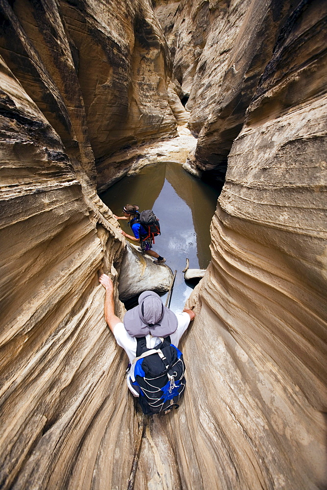 Jeff Crystol foreground and Josh Williams in backround descending Miners Hollow or Knotted Rope Canyon, San Rafael Swell, Utah.