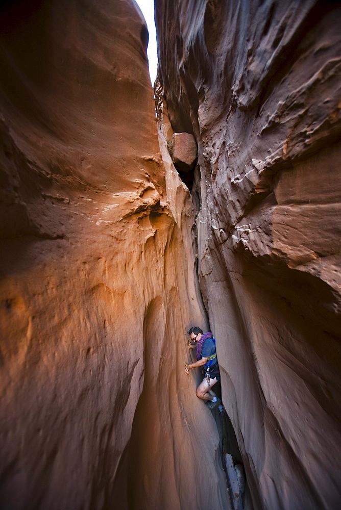 A man chimneying down a slot canyon, Utah.