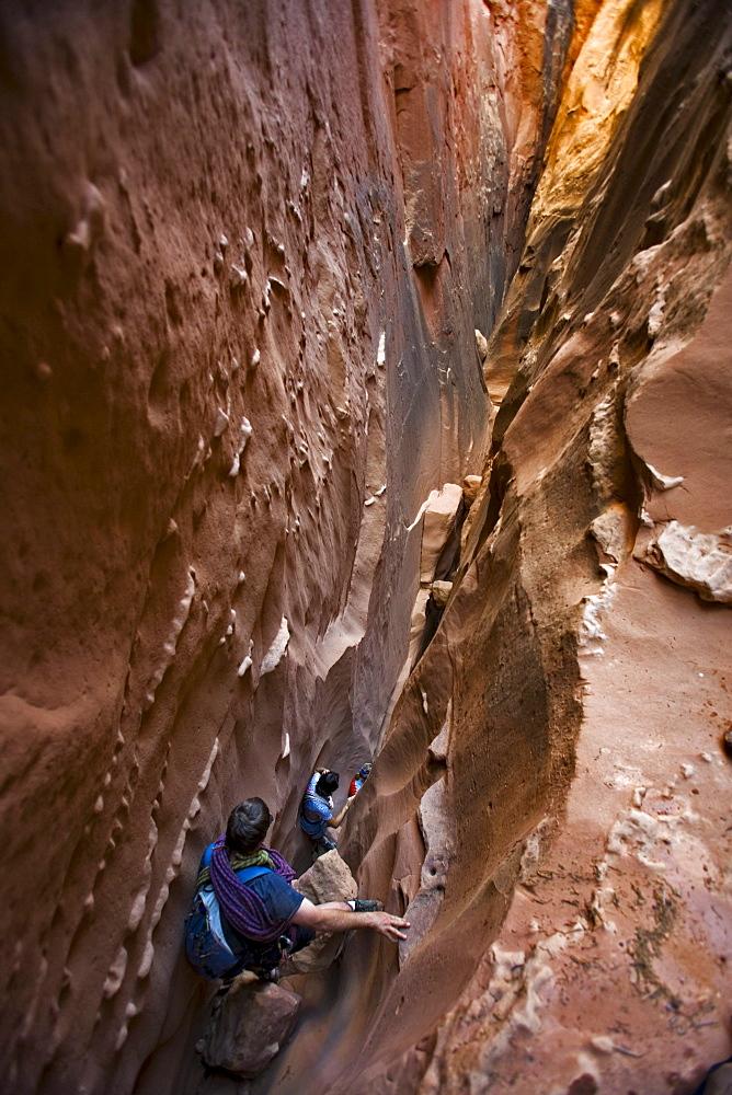 Three people descending a slot canyon, Utah.