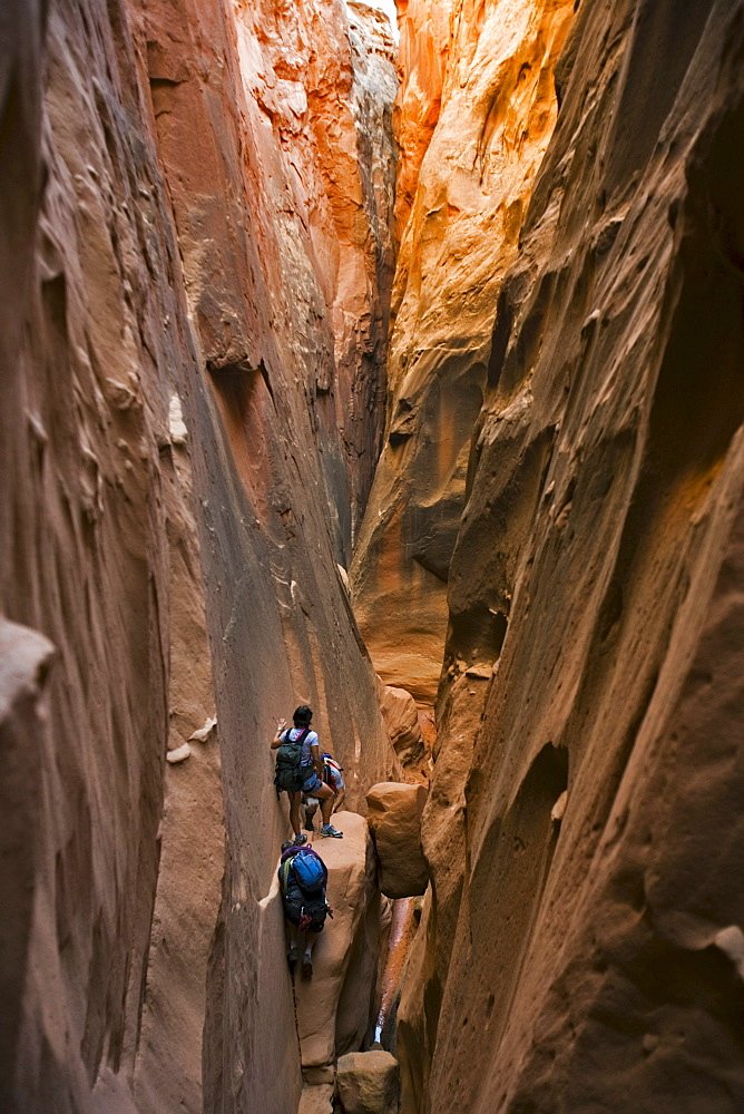 Three people in a slot canyon, Utah.