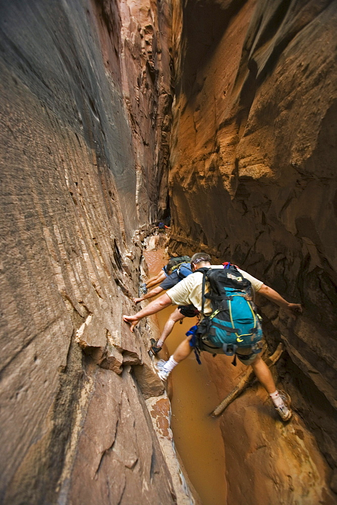 Three people stemming between two walls above water in slot canyon, Utah.