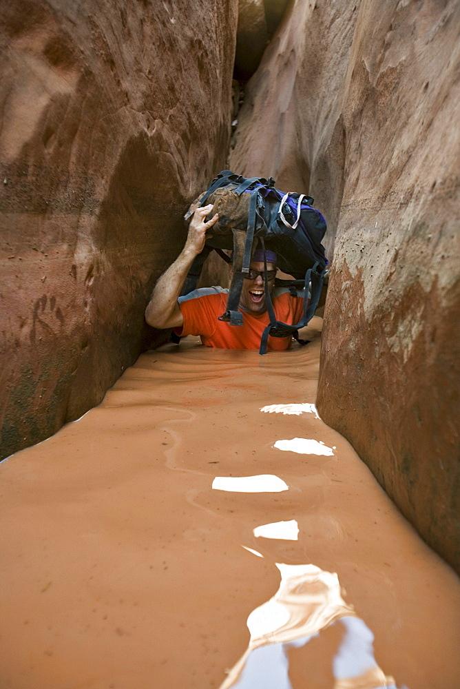 A man wading through water in narrow canyon, Utah.