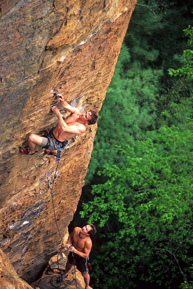 Two men rock climbing on sandstone in a Kentucky forest.