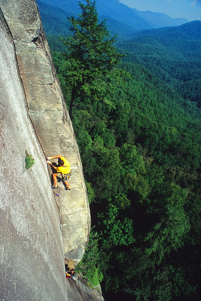 Two men rock climbing on a large granite face in North Carolina.