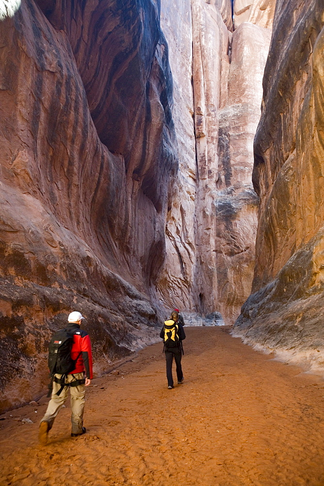 Three hikers in canyon, Arches National Park, Moab, Utah.