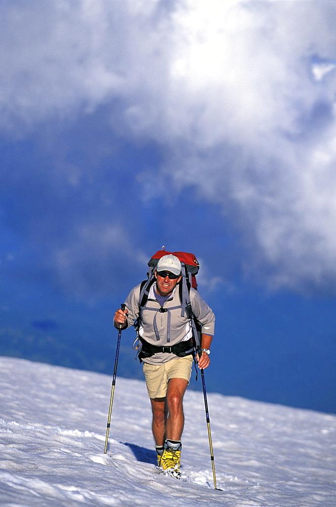 Climber in shorts with trekking poles summits Mount Rainier, Washington.