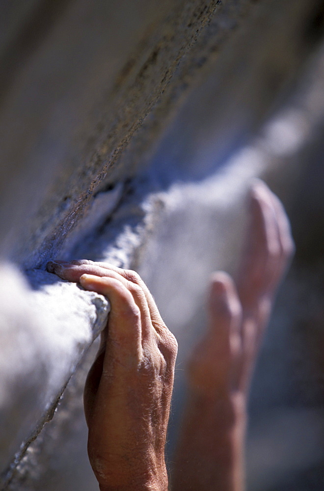 Close up of a climber's hands holding onto and reaching for a small ledge in Cordillera Blanca, Peru (Selective Focus).