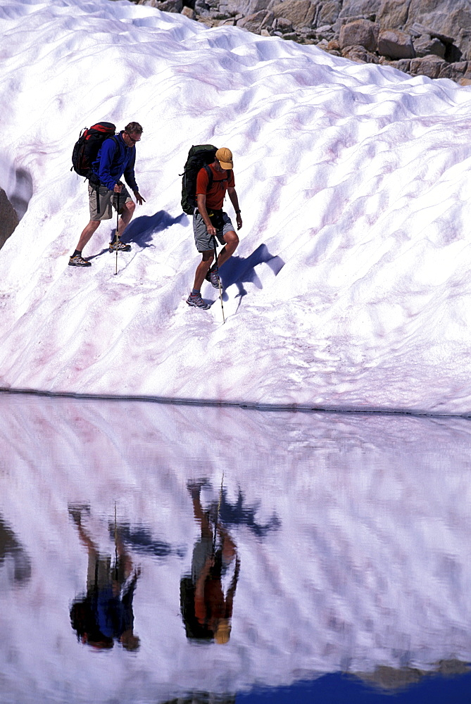 Two hikers on a glacier reflecting in a lake in Eastern Sierra Nevada mountains, California.