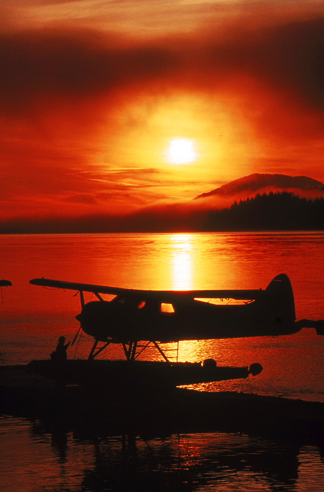A pilot prepares his float plane (amphibious) for take-off at sunrise in Ketchikan, Alaska.