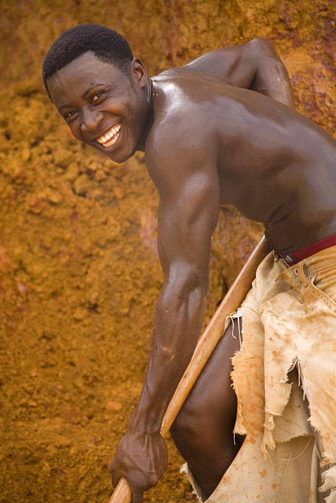 Young Liberian Man shovels red soil