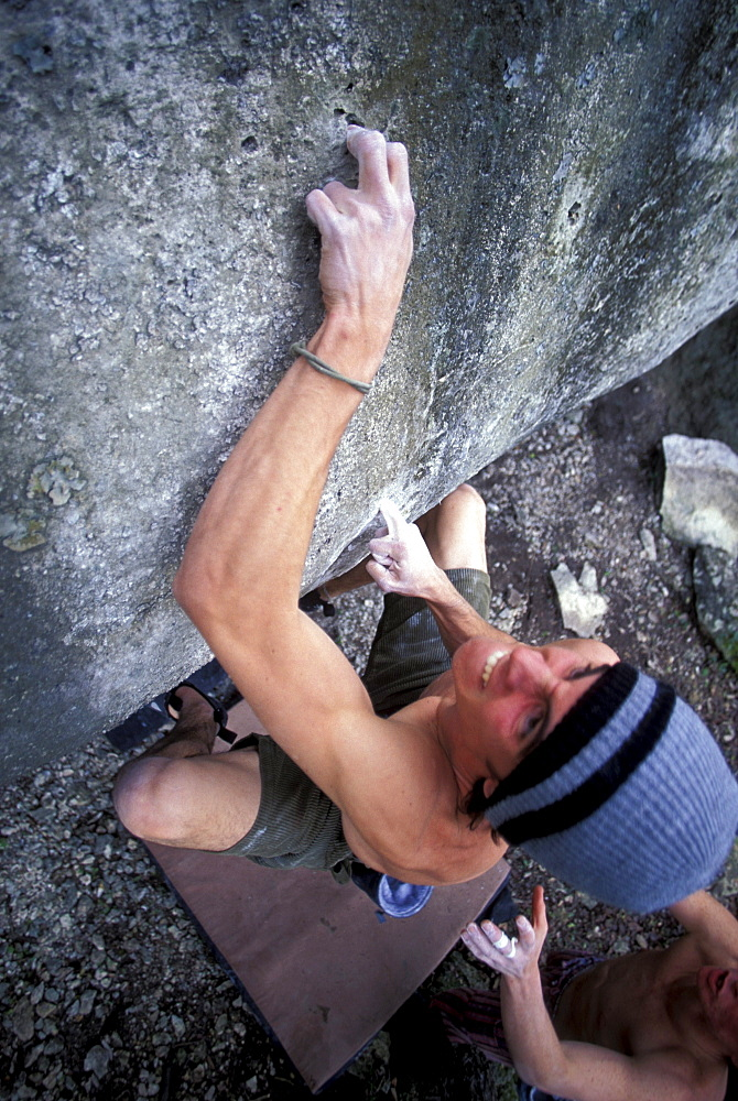 Climber using a finger hold while bouldering near Austin, Texas.