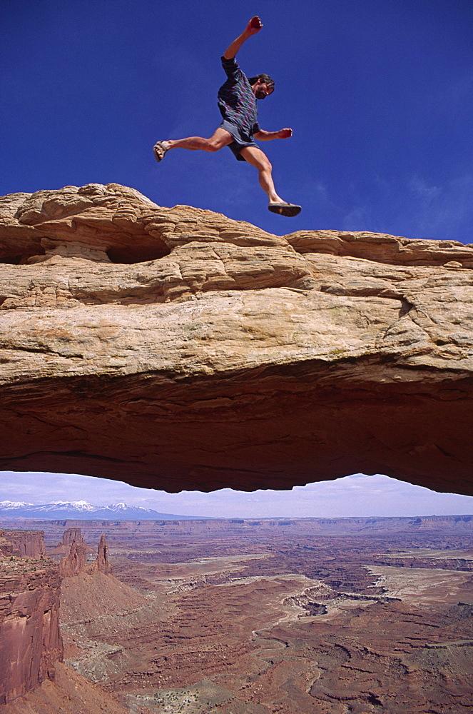 Cliff Leight, a desert adventurer, leaps above Mesa Arch